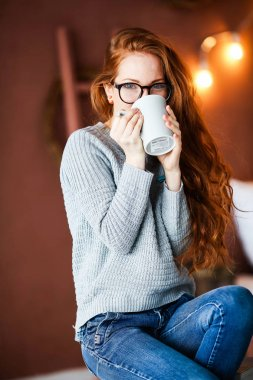 beautiful  young red haired woman posing with mug