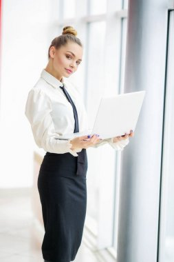 beautiful business woman posing with laptop