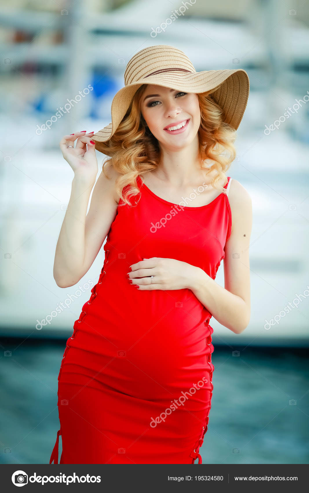 46353ed383689 Beautiful blonde pregnant woman wearing red dress and straw hat — Photo by  ...