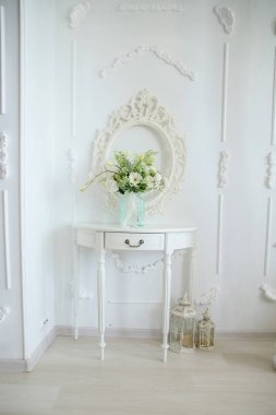 A Versailles table against a white wall with a vase of flowers on the table