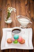makronky a šálek kávy na stole