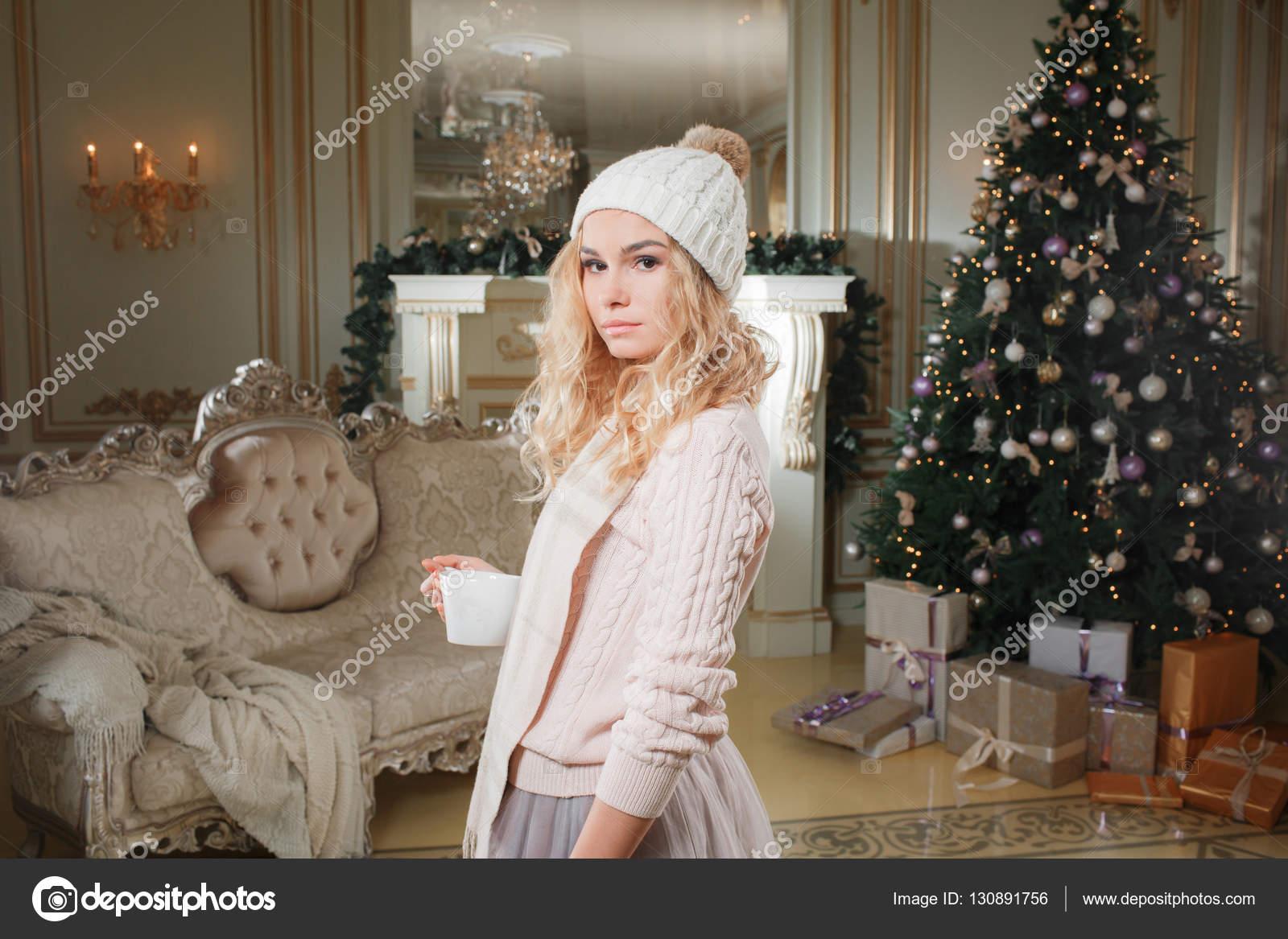d8efd03bad Noche de Navidad. Joven hermosa mujer rubia con taza de café en  apartamentos clásico decorado una chimenea blanca