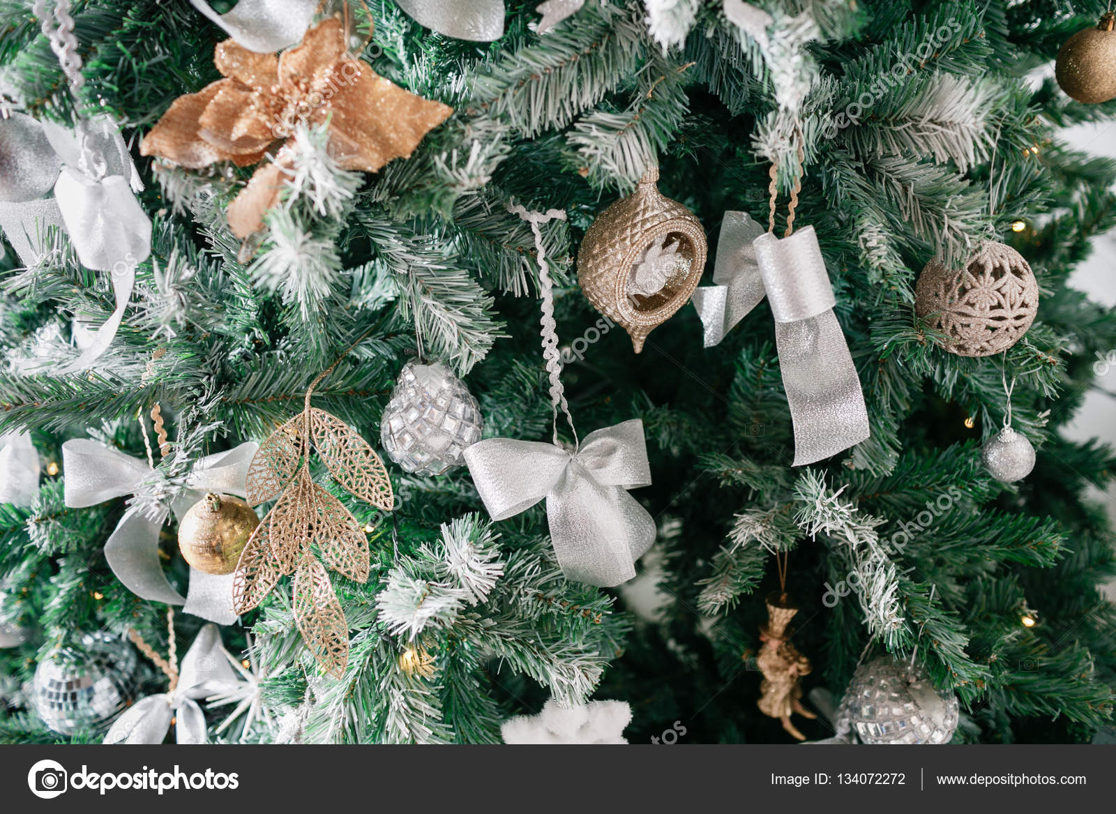 Close up of Christmas tree with ornaments baubles, bow, snowflakes ...