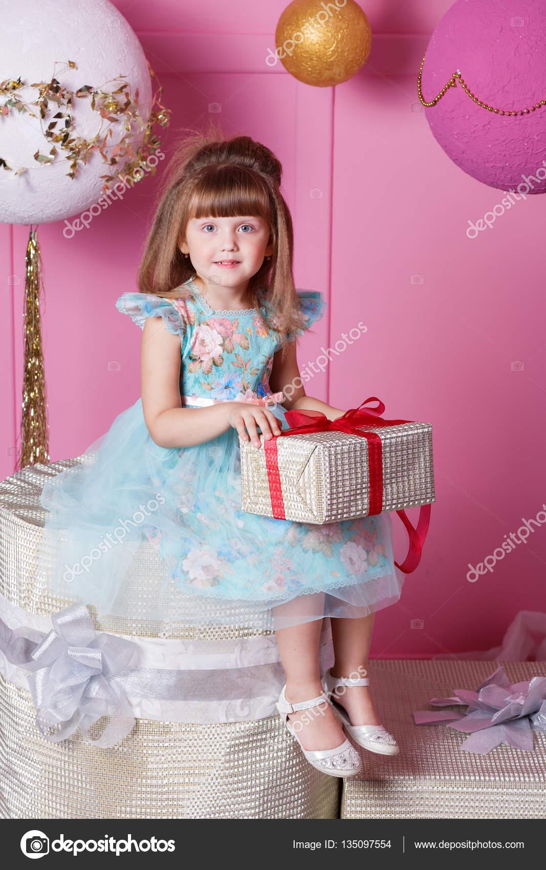 Linda niña de 4 años en un vestido azul. Regalo de la tenencia del ...