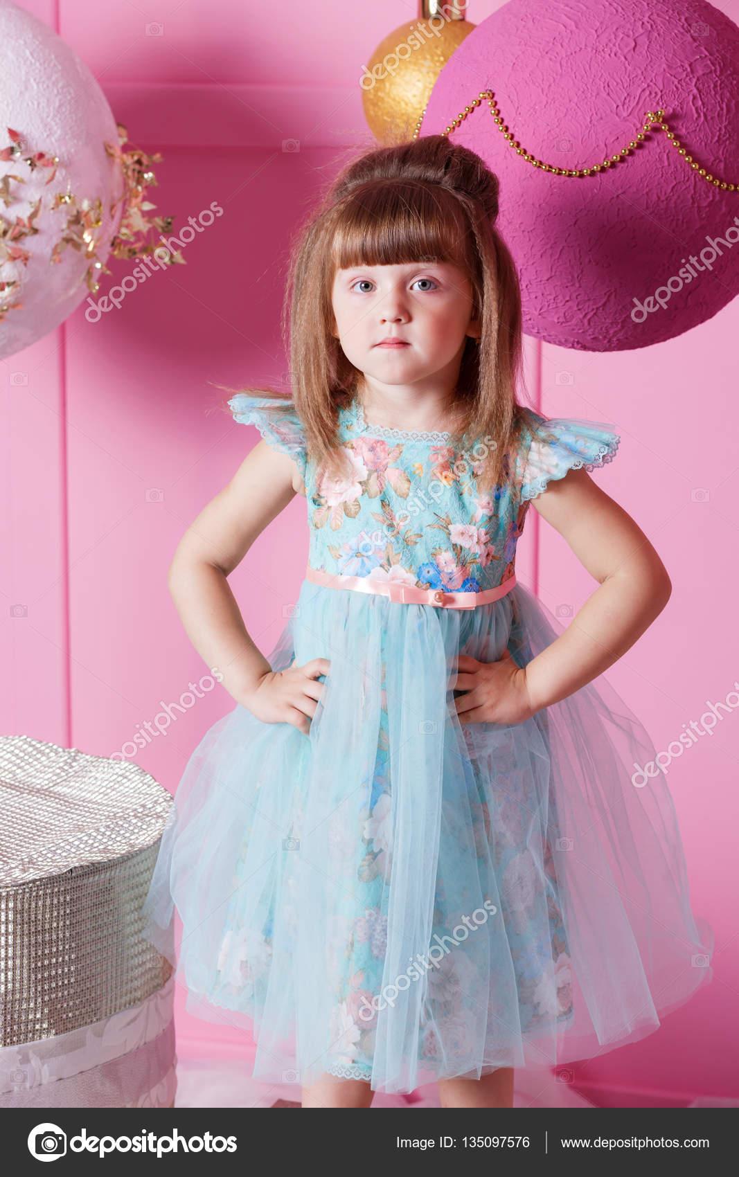Linda niña de 4 años en un vestido azul. Bebé en cuarzo rosa sala ...