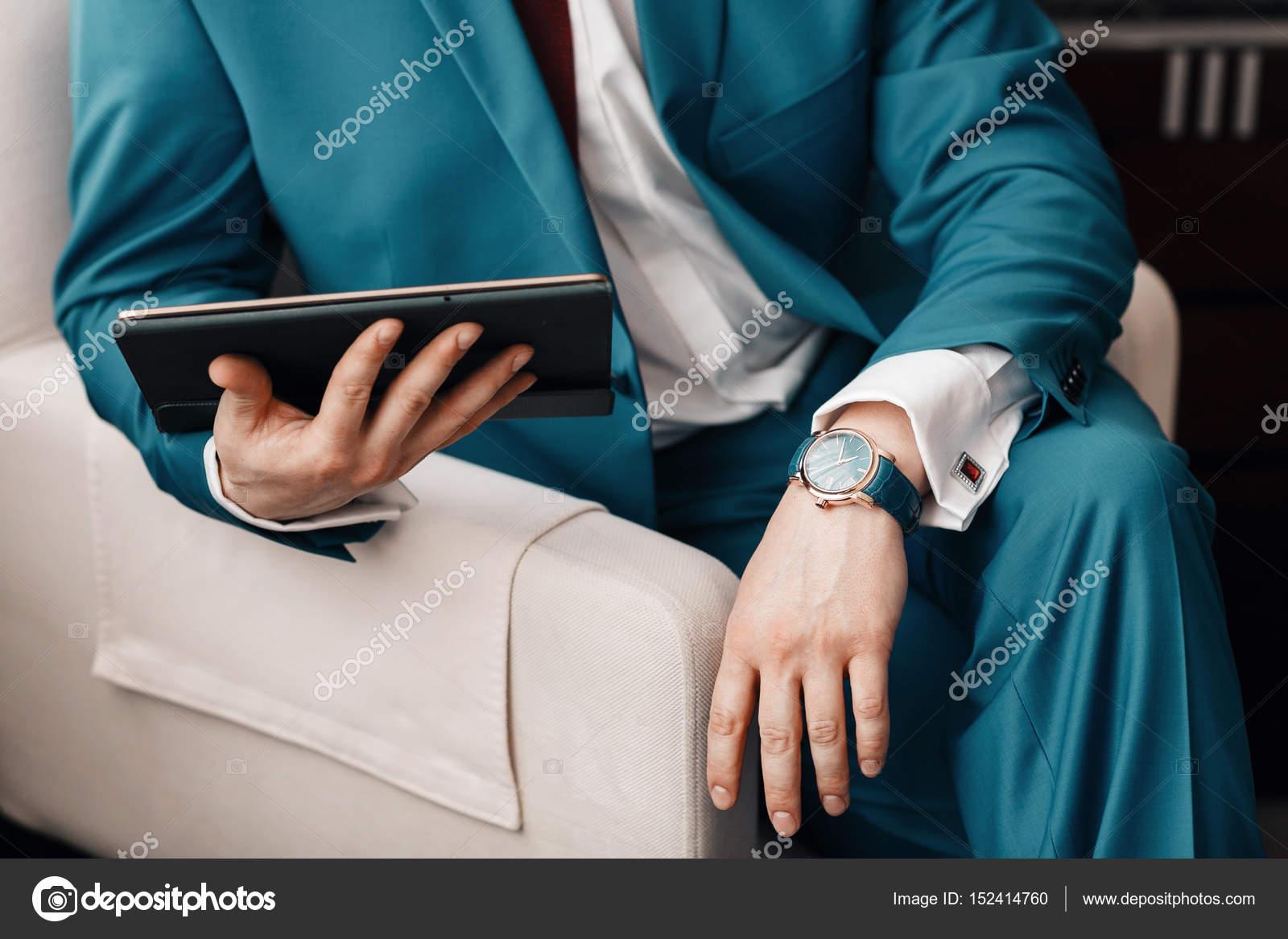 f2eec9731754 ... ενώ κάθεται σε έναν καναπέ σε ένα μπλε κοστούμι. στο χέρι ακριβά  μηχανικό ρολόι με δερμάτινο λουράκι. Πουκαμίσα με μανικετόκουμπα — Εικόνα  από ...