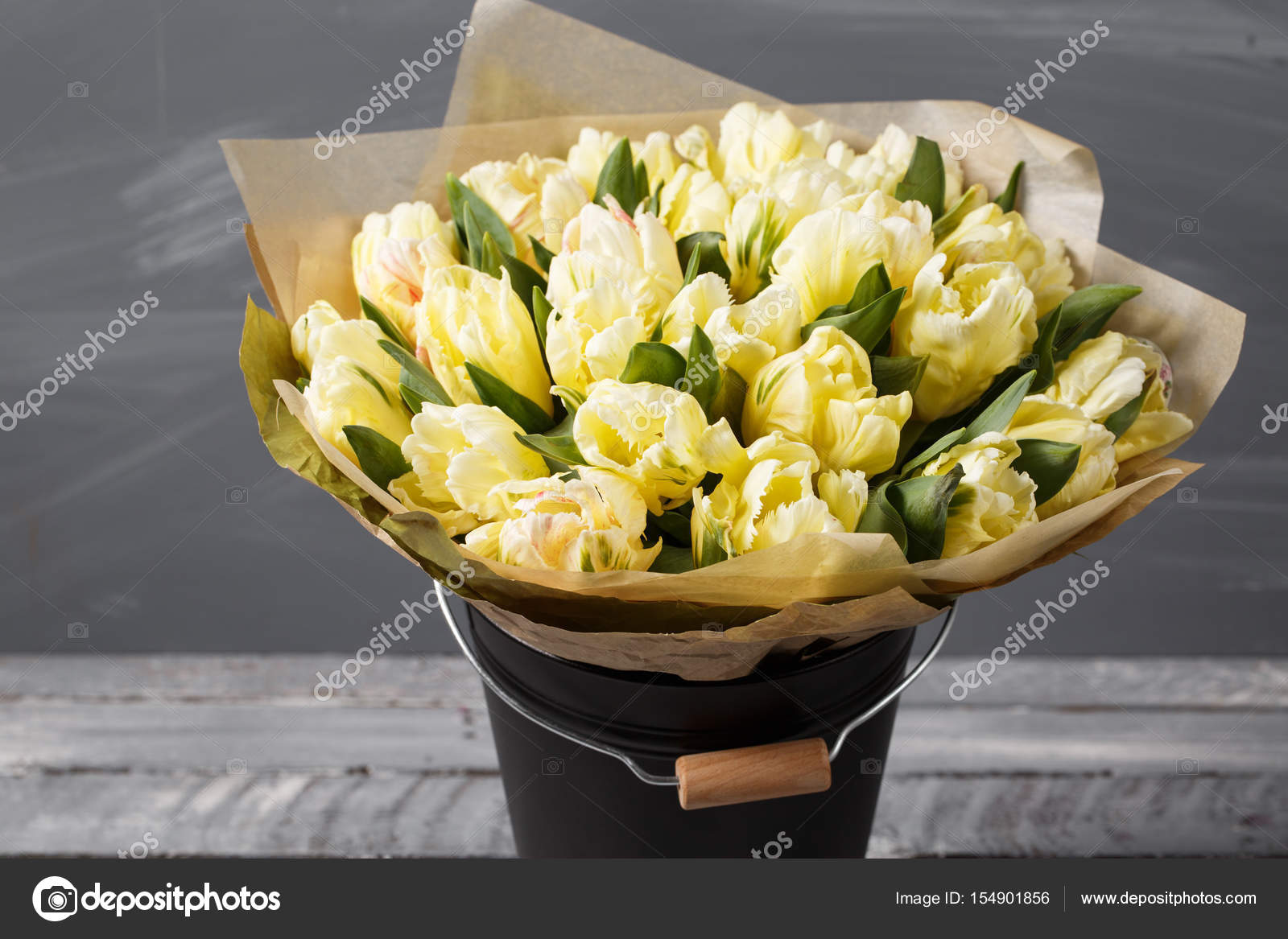gently yellow pastel colors tulips in vase on wooden table. Gray ...