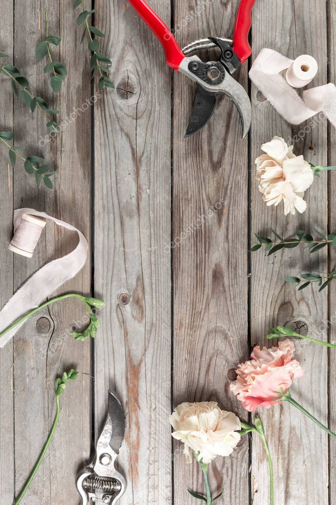 flowers and garden tools. The florist work table with accessories gray wooden background.
