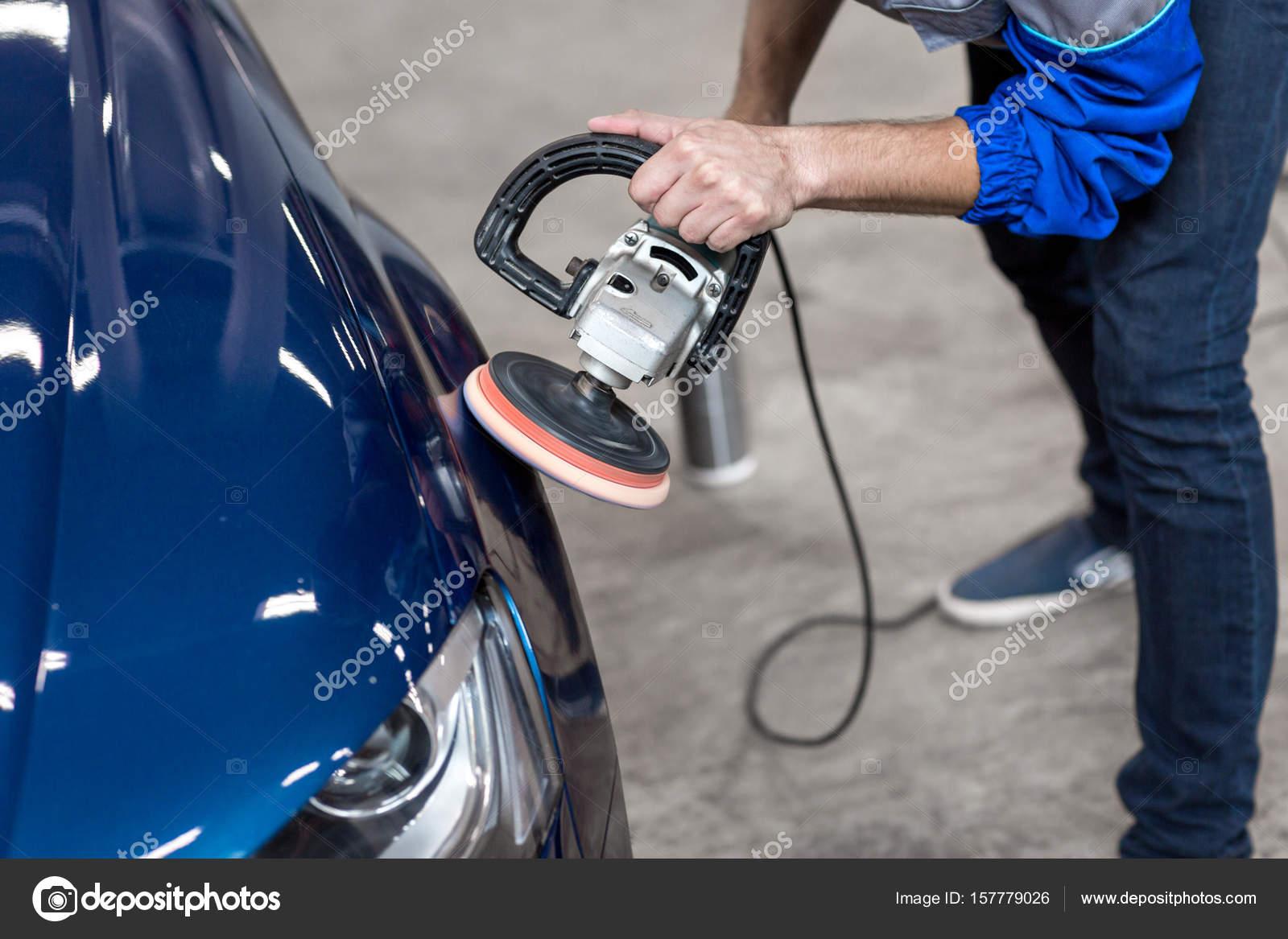 Professional mechanic using a power buffer machine for
