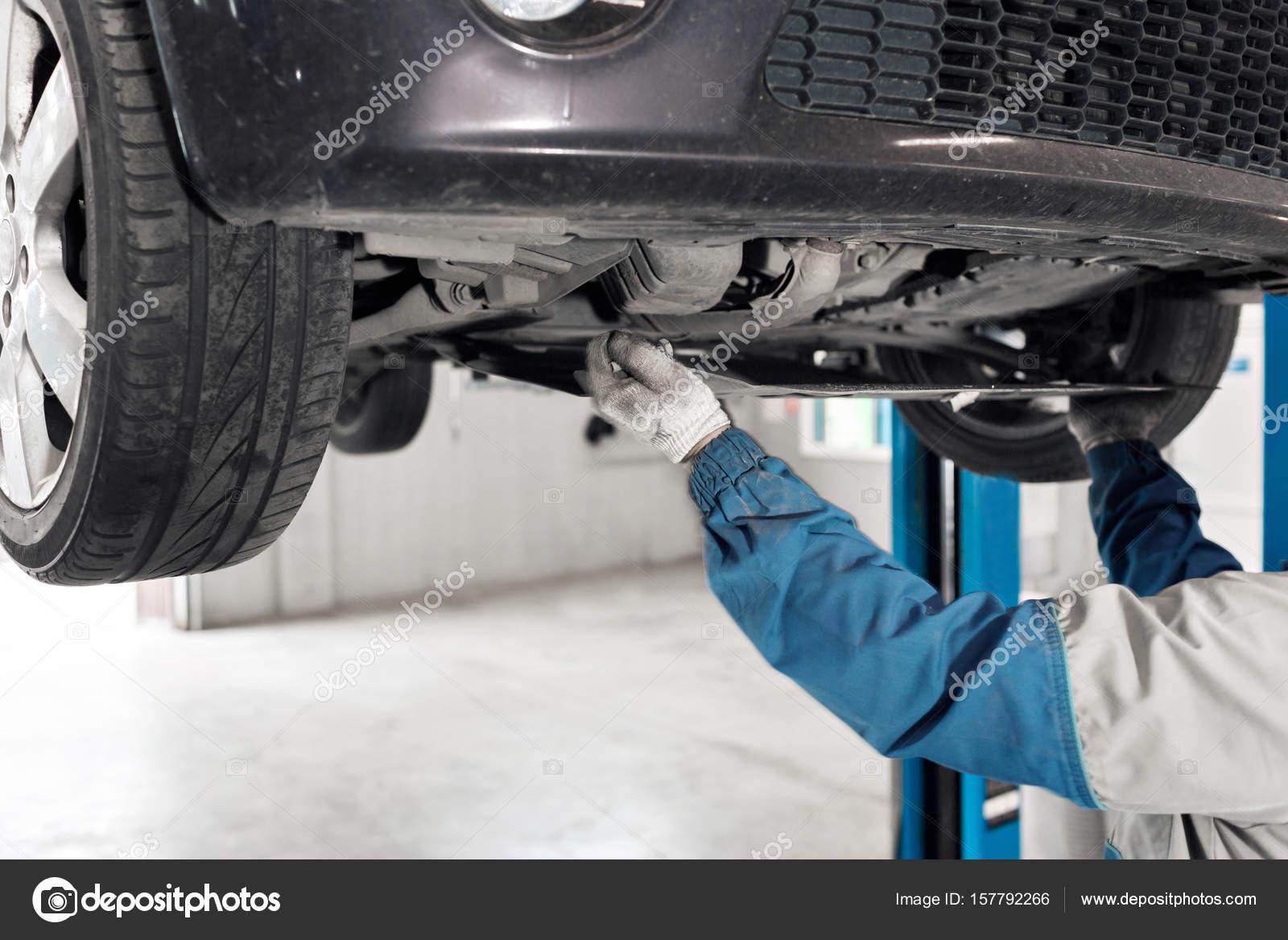 Kfz-Mechaniker arbeiten unter dem Auto auf einer Hebebühne ...