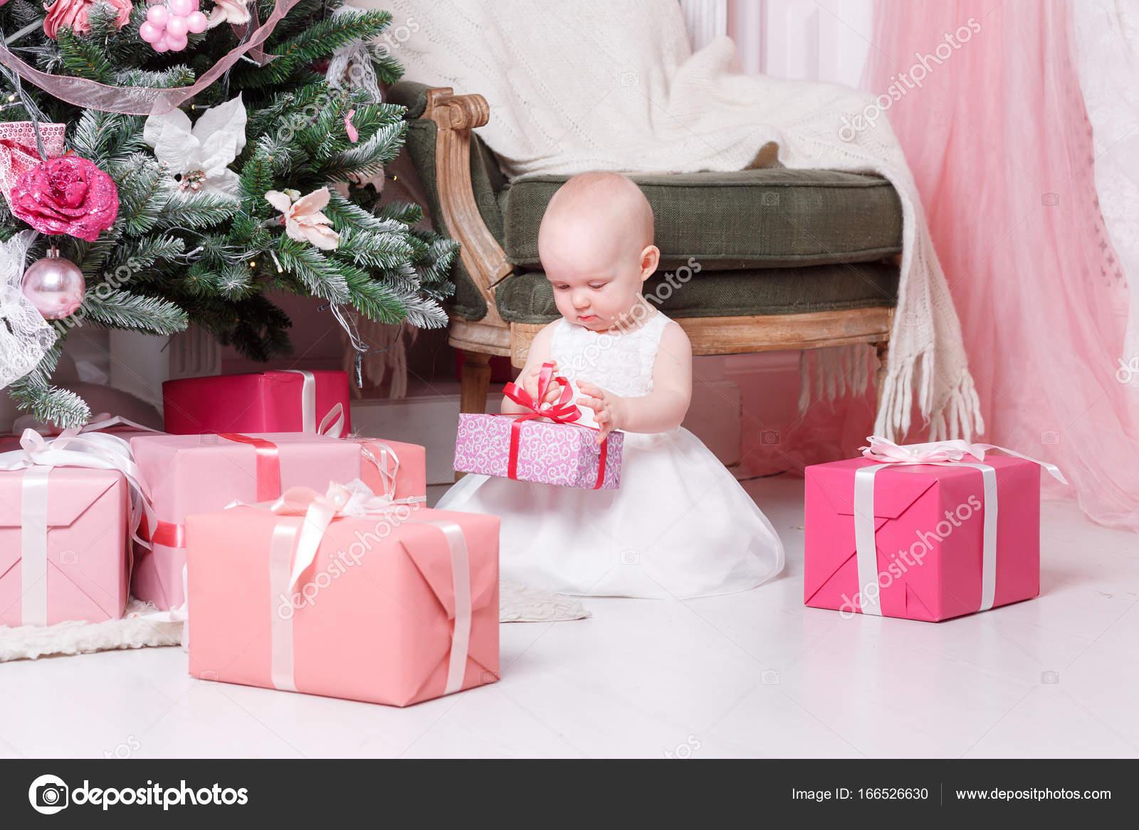 Noche de Navidad. Niña sentada y desenvuelve regalos. vestido blanco ...