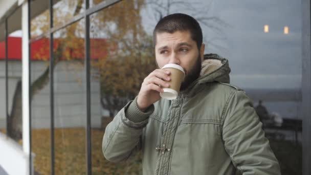 schöner junger bärtiger Mann hält eine Tasse in der Hand. Kaffee oder Tee im Herbst im Freien trinken