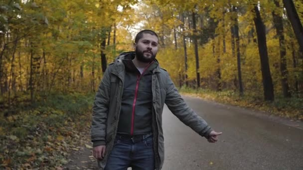 Young man hitchhiker with standing on a highway in autumn. Adventure and tourism concept