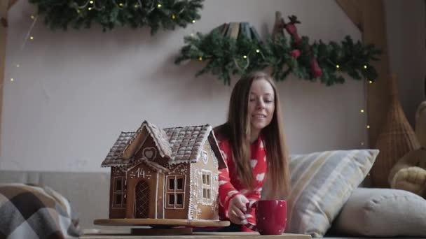 Kellemes karácsonyi ünnepeket és boldog ünnepek. Fiatal nő ivás meleg tea karácsonyi sütik