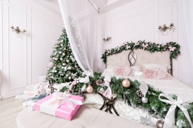 Cozy Christmas home interior. New year decoration. bright bedroom room with large double bed.