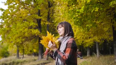 bouquet of the yellow leaves. Autumn girl walking in city park. Portrait of happy lovely and beautiful young woman in forest in fall colors.