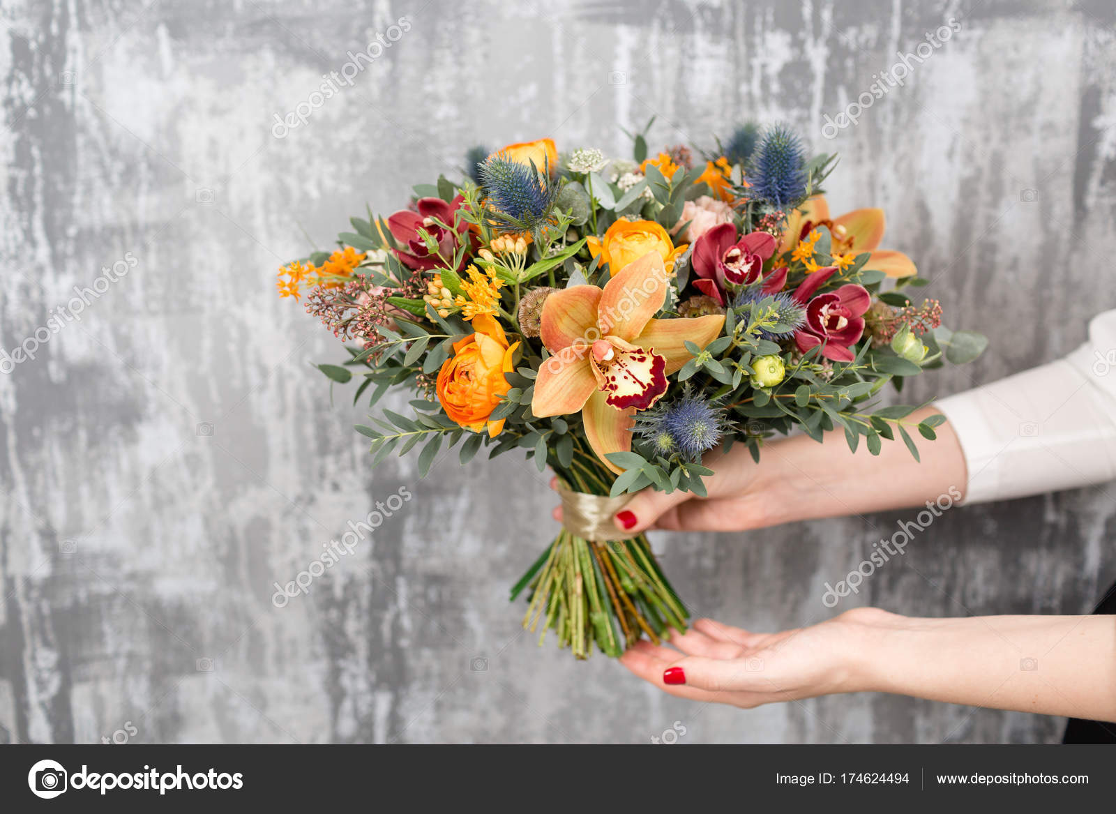 beautiful wedding bouquet of mixed flowers in woman hand. the work ...