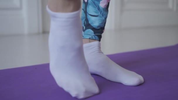 Heimfitness. junge Frau wärmt sich vor dem Training auf und macht Übungen zur Dehnung ihrer Muskeln und Gelenke
