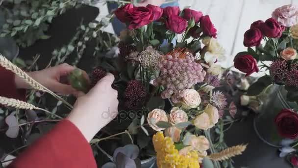 Hlavní třída ženské květinářství v práci s kytice. Dívka dělat kytice různých podzimních květin. Obchodní žena květiny v květinářství