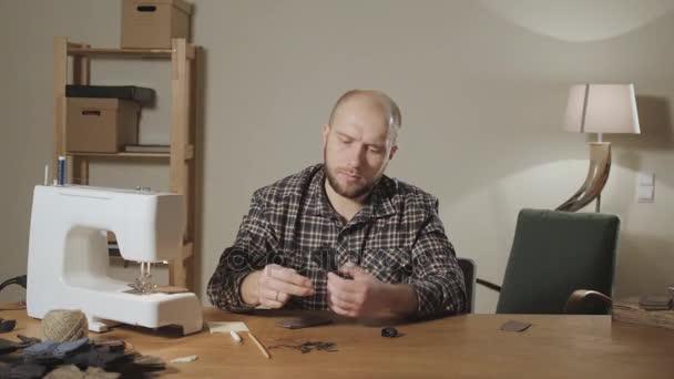 gut aussehender junger Mann, der als Schneider arbeitet und in einem Textilatelier eine Nähmaschine bedient. macht Fliege