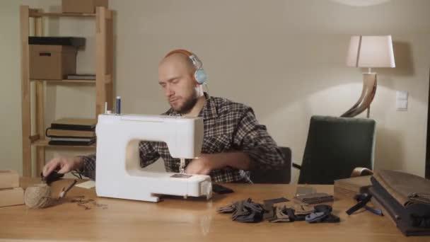 junger Mann Kopfhörer und hört Musik. Arbeit als Schneiderin und Einsatz einer Nähmaschine in einem Textilstudio. macht Fliege
