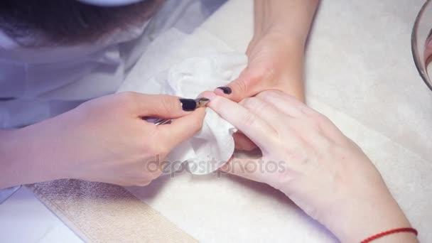 Closeup prsty a nehty manikúra odborník v salonu krásy. Manikérka vymazat profesionální kleštičky na manikúru a pedikúru.