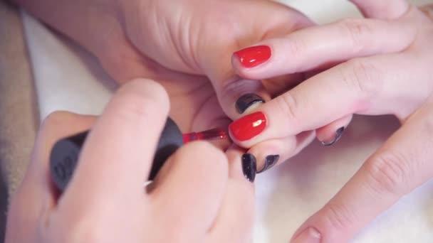 Manikúru. Master se vztahuje lak na nehty gel v lázních. Closeup prsty a nehty odborník v salonu krásy.