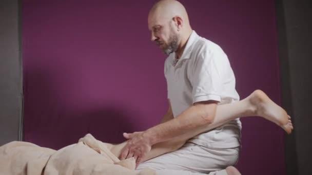Massaggio benessere del piede. Chiuda in su della osteopata che fa massaggio manipolativo. Mani delluomo che massaggia donna. Concetto di centro Spa