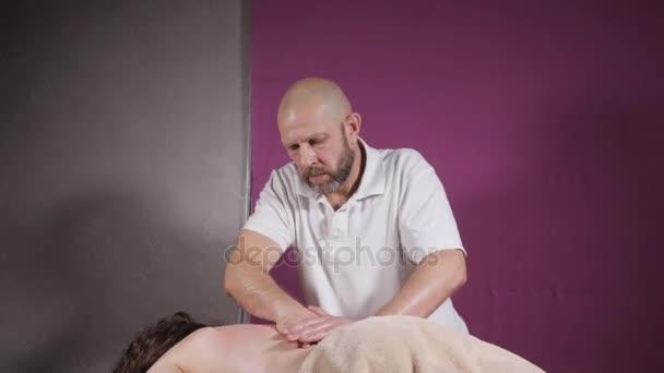 Detail masér ruce. Masáž páteře a šíje, uvolněné pacienta se těší. nízký klíč. Člověk ruce masážní žena. Lázeňské centrum koncept
