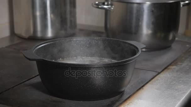 kuchař kuchař přidává ingredience. Tradiční hovězí vývar se zeleninou, kosti a ingredience v hrnci, vaření recept. Polévka v hrnci vaření s naběračkou na tmavém pozadí kamene. Pohled shora