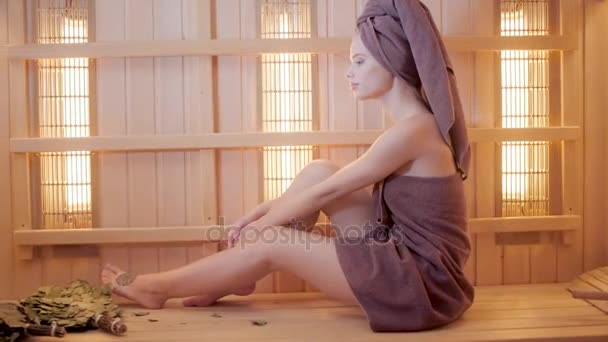 Mladá žena, relaxaci v sauně, oblečený v ručníku. Interiér nové finské sauny, infračervené panely pro lékařské procedury, klasické dřevěné sauny.
