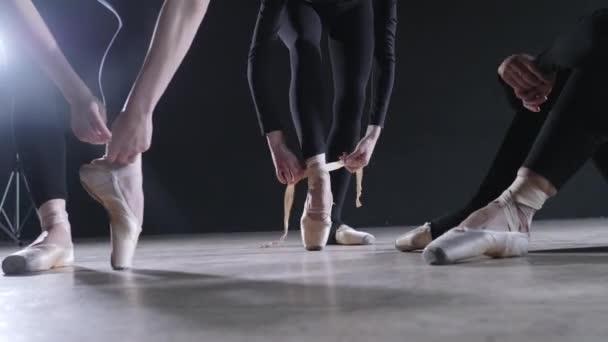 Spitzenschuhe aus nächster Nähe. junge Ballerinas. Frauen bei der Probe in schwarzen Bodys. Vorbereitung einer Theateraufführung