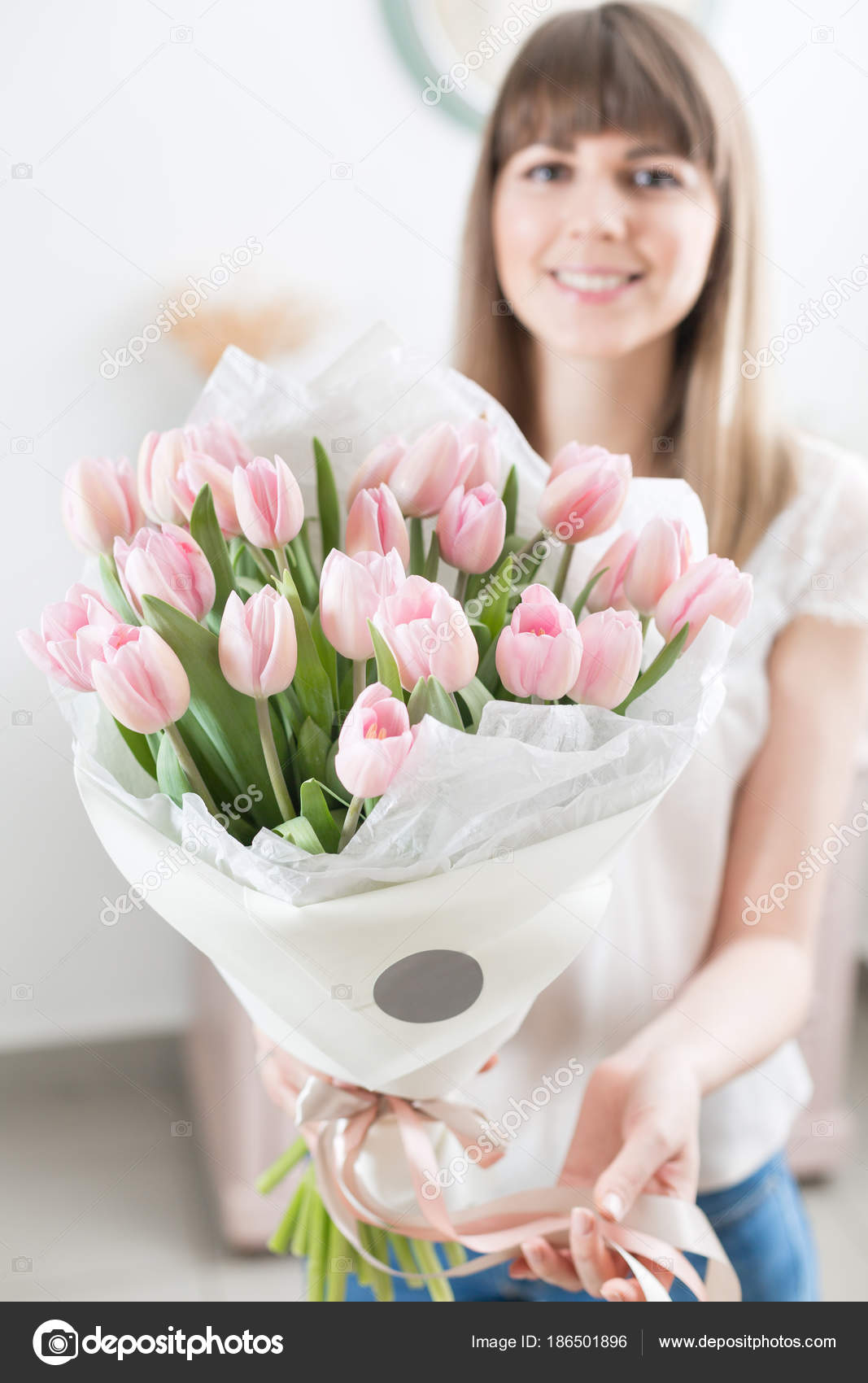 Sunny spring morning young happy woman holding a beautiful bunch of young happy woman holding a beautiful bunch of pink tulips in her hands present for a smiles girl flowers bouquet photo by malkovkosta izmirmasajfo