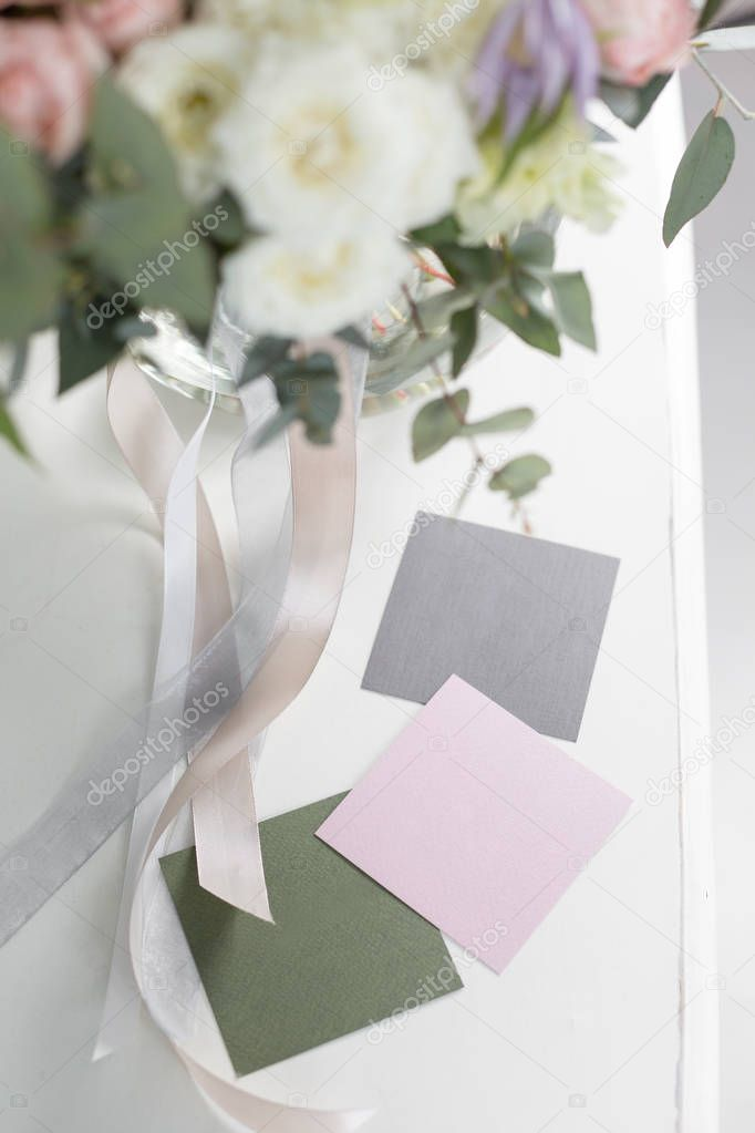 Blank business cards, copy space. Sunny spring morning in living room. Beautiful luxury bouquet of mixed flowers in glass vase on wooden table.