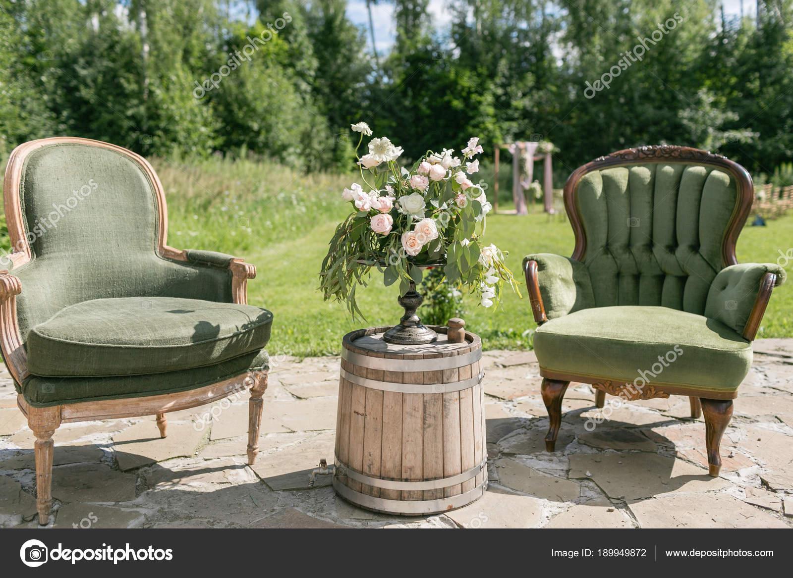 Sedie Depoca : Sedie depoca in legno e tavolo con decorazione floreale in giardino