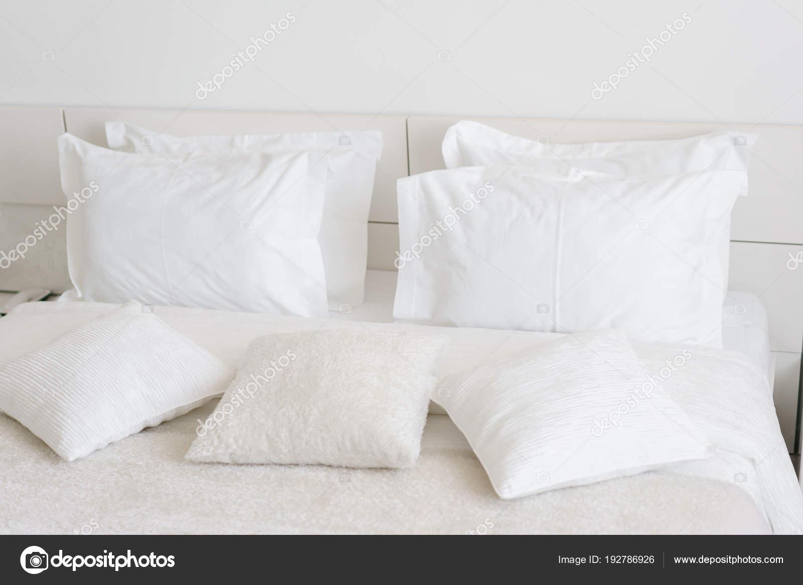 Confortevoli e morbidi cuscini sul letto. Primo piano bianco ...