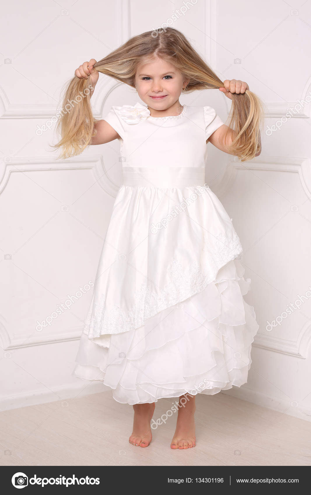 Little lady in dress holding her hair. White background — Stock ...