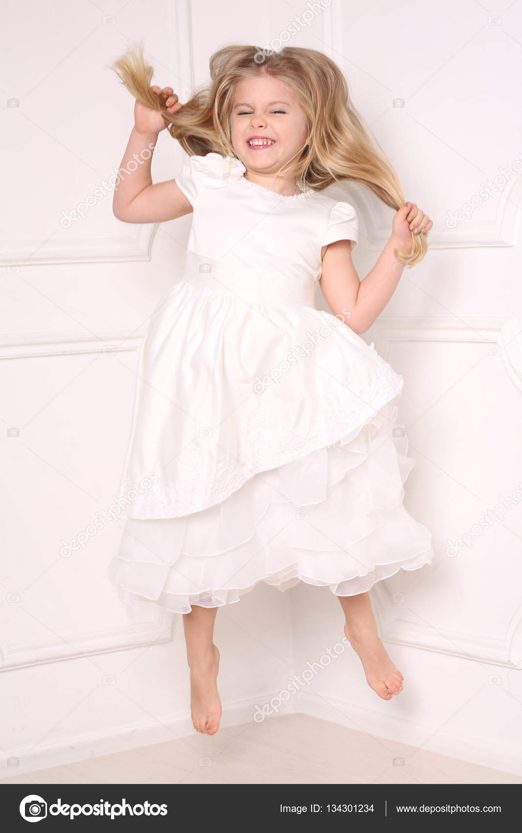 Child in dress jumping and holding her hair. White background ...