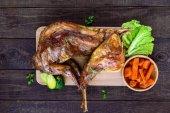 Pečená celá králík na dřevěné desce s pečených mrkví a Růžičková kapusta na tmavém pozadí. Slavnostní jídlo. Pohled shora.