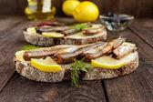 Fotografia Panino con il capelin di pesce affumicato (spratti), limone su pane nero di segale. Uno spuntino su un tavolo di legno scuro