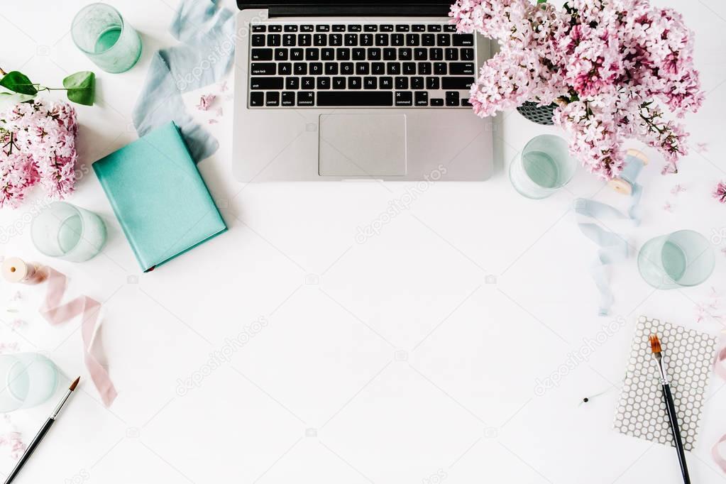 Workspace with paintbrush, laptop, lilac flowers bouquet
