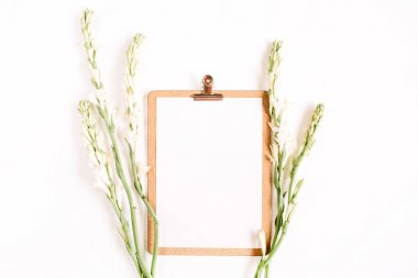 Clipboard and white flowers.