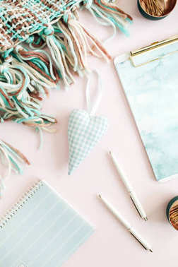 Female workspace with clipboard, diary, stationery on pale pink background. Top view feminine concept.