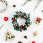 Vánoční složení. Dovolená věnec rám vyrobený z větve jedle s kužely, jalovec, zvony, skleněné vánoční koule na bílém pozadí. Plochá ležel, top view holiday dekorace koncept