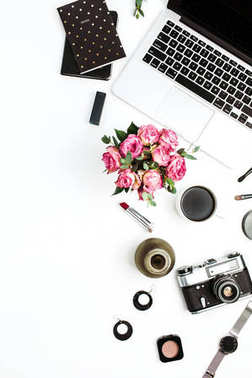 Woman fashion home office desk. Workspace with laptop, rose flowers bouquet, retro camera, accessories and cosmetics on white background. Flat lay, top view stylish female concept.
