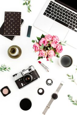 Female home office desk. Workspace with laptop, rose flowers, retro camera, accessories and cosmetics on white background. Flat lay, top view fashion blog concept.
