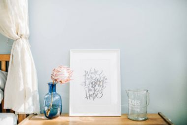 Photo frame with calligraphic quote Where there's light there's hope, protea flower in vase in front of pastel blue wall. Mock up frame.