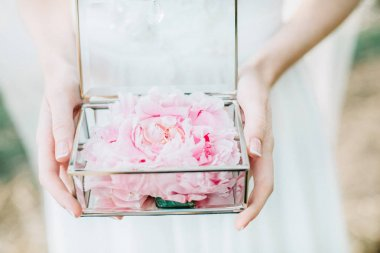 Bride holding glass casket with peony flower buds and wedding rings. Bridal fashion background.
