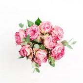 Růžové květy růže kytice na bílém pozadí. Pohled na ploché ležel, top. Minimální jarní květinový koncept