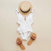Plochá laických letní módní složení. Dámské plavky, slámy a pantofle na pastelové béžové pozadí. Koncept minimální beach byt ležel, horní pohled